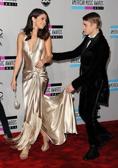 The couple made quite an appearance at the 2011 American Music Awards. Bieber, who was dressed in a dapper tux, held his gal's dress as they walked the red carpet then showered her with kisses.