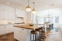 Beautiful kitchen features a pair of Small Brass Hicks Pendants illuminating a white center island ...