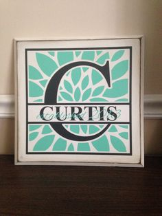 """Last name monogram with flower design and established date on 12"""" x 12"""" distressed board."""