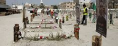 Two Saudi men walk through a cemetery where religious flags, photographs, and flowers mark graves of victims of a suicide bombing, claimed by the Islamic State group, in Qudeeh, Saudi Arabia. (Hasan Jamali/AP)