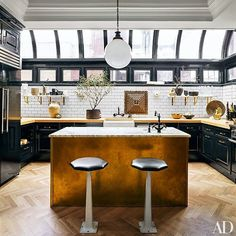 The kitchen is outfitted with cabinetry and butcher-block countertops by Fanuka, while the island is clad in unlacquered brass and topped with Breccia Imperiale marble | archdigest.com