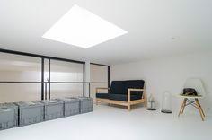 今は収納スペースとして使われているロフト。トップライトから落ちた光が白い床で反射して、左のリビングと右手にある寝室まで拡散する。
