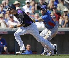 Colorado Rockies' Tyler Colvin, left, is tagged out by Chicago Cubs shortstop Adrian Cardenas