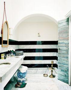 Sunken marble bathtub with horizontal stripe tile detailing.