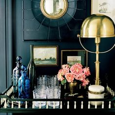 Dark walls, fresh pink flowers, and brass accents create a chic bar scene. #TGIF  Mary Rozzi