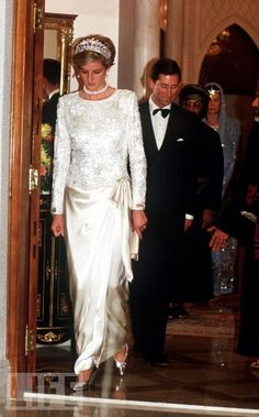 November 1986:  Charles & Diana attend a dinner in Oman w/ Diana wearing a luxurious ivory satin & lace Emanuel evening gown. The wrap-over skirt ties onto one hip.