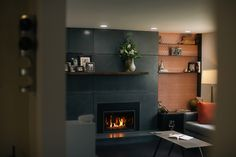 The retro wallpaper really brings out the warmth of the steel bookshelves and concrete fireplace.