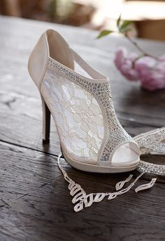 White lace accents. Open toe bootie heel with leather surroundings.