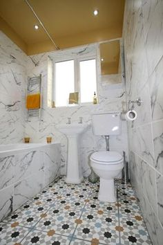 Bijou bathroom with traditional fittings, marble effect wall tiles and Moroccan style geometric floor tiles designed by Amelia Wilson Interiors Ltd