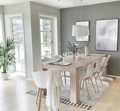 dining room with light gray walls, light wood table and floors, white chairs and decor, and lots of natural light