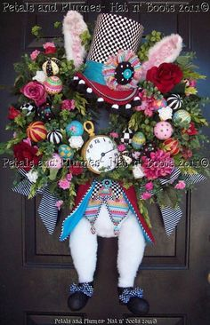 Mad Hatter Wreath. He is made from Faux fur, with two colors used on his ears and they are wired. Ornaments and eggs are all hand embellished and his Vest and Waist Coat is hand made with coordinating colors. The Button and Egg beads on his Vest are also hand made painted along with the Clock . He measures 37 x 28 x 10.
