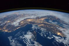 Space Station Flyover of the Mediterranean: Nighttime photograph from low Earth orbit of Mediterranean showing clouds and city lights
