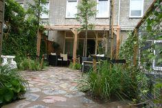 Diemelgroenvoorzieningen  Hier een overzicht van de tuin met een bestrating van flagstones. Door de natuurlijke uitstraling van de bestrating en de losse beplanting met hierboven de Gleditsia's ontstaat een heerlijke ruimte om tot rust te komen