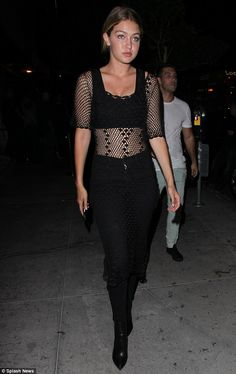 Style statement: Gigi Hadidflashed her taut in a black fishnet-panelled top as she attended her sister's hen party in West Hollywood, California, on Friday evening
