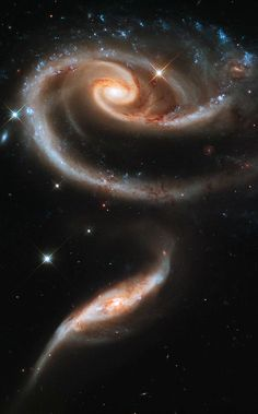 """⚘A Cosmic Rose of Galaxies, Arp 273 in the Andromeda Constellation - the distorted shape of the larger """"bloom"""" galaxy is thought to have been caused by the smaller """"stem"""" galaxy passing through the larger... 