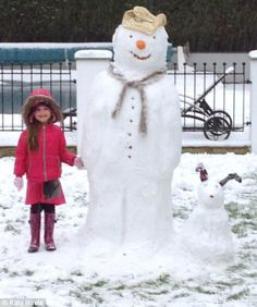 Tall order: A little girl stands with her new friends Elise the snowman and Lexi the snowdog in Essex