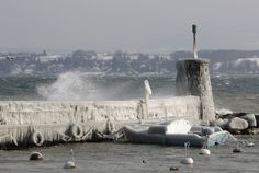 ✶Temperatures plumet up to -22 Fahrenheit across Europe in the February winter of 2012. A frozen boat is moored next to an ice covered wall on a windy winter day in the harbour of Versoix near Geneva, SWITZERLAND✶