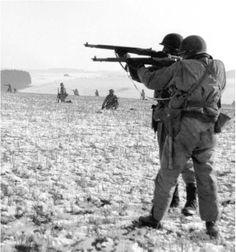 American troops firing M1 Garand rifles near Bastogne, Belgium, 1944