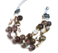 The sea urchin beads in this handmade bracelet are gorgeous. They have these bands of dark neutral and subtle mauve. Combined with the pearl looking brown lip shell, this is the perfect summer look. This bracelet has sold, but contact me anytime to make a similar piece.