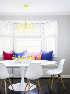 White breakfast nook with patterned curtains, colorful pillows, and modern furniture
