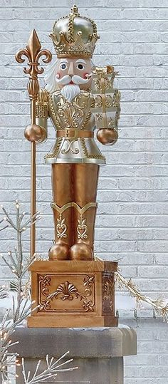 Sharply dressed in his finest uniform, our St. Christopher Nutcracker is a stately soldier standing guard from a golden platform. This handsome officer is handpainted by skilled artisans and holds a staff in one hand and a stack of presents in the other.