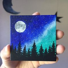 This painting consists of a blue and green night sky full of stars, with the Milky Way visible. The painting is completed with the signature full moon and silouette of pine trees Small Canvas Paintings, Easy Canvas Art, Small Canvas Art, Mini Canvas Art, Easy Canvas Painting, Small Paintings, Galaxy Painting, Blue Canvas, Night Sky Painting