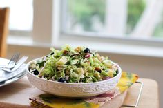 Shaved Brussels Sprout Salad with walnuts, avocado, blueberries, apples, and a homemade dressing -- you won't need the cheese in this recipe