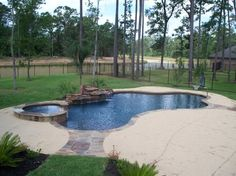 Residential Pool #005 - 41 foot Pool and Custom Spa with stacked stone spillway. Features include: natural moss rock waterfall, Oklahoma flagstone coping and fascia on back of spa, flagstone inlays in the decking, spray deck with custom step, removable basketball goal.