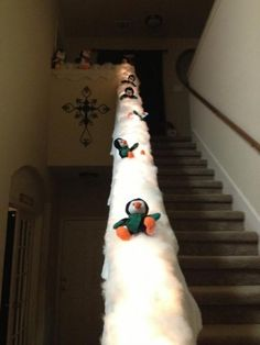 Christmas stair case banister decoration: Penguins sledding down on snow.