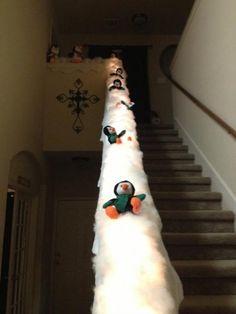 Christmas stair case banister decoration: Penguins sledding down on snow.