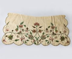 Apron, probably England, c. 1725-1750. Cream silk taffeta, hand embroidered with a Jacobean floral pattern with polychrome silk floss and bronze metallic floss. The scalloped edges arte trimmed with corded floss.