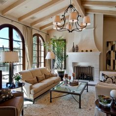 California Mediterranean- arched doors, iron and glass table, fireplace. Neutral color palette.