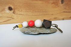 Schlüsselanhänger mit verschiedenen Holzperlen in den Farben dunkelbraun, naturfarben,rot und goldfarben, aufgefädelt auf ein khaki-goldfarbenes Lederband. Der Schlüsselring ist bronzefarben.  Gerne kann ich diesen Schlüsselanhänger auch individuell nach deinen Wünschen zusammenstellen, z.B. mit anderen Perlen oder in einer anderen Länge.