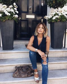 Caroline Receveur looking stylish in navy top, denim jeans and Balenciaga handbag in London.