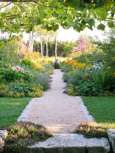Unfussy gravel offers a casual surface beneath a walker's feet.    -- Plants spilling over the walkway edge give the garden an established, lush feel.    -- Stone pavers act as edging to keep loose gravel inside path boundaries.    -- A large pot serves as a focal point to mark the end of the walkway.