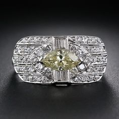 This unique and enchanting vintage 'cigar band' ring glistens and glows with a bright and sizzling natural intense fancy yellow marquise diamond, weighing .79 carat. The diamond is presented in a sparkling diamond frame, composed of baguette and round diamonds, atop a gently curved five-row diamond band ring which lays low and snug around the finger. A singular and sensational Art Deco jewel - circa 1930s.