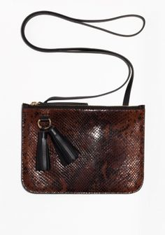 A skinny, easy-to-wear bag made from polished snakeskin textured leather, featuring luxe tassels and gold-tone details.