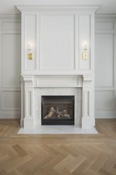 Beautiful living room with gray wainscoting paneled walls and fireplace accented with a pair of TT Single Wall Lights in Hand Rubbed Antique brass over a marble fireplace surround and hearth framed by herringbone hardwood floors.