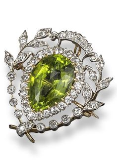 An early 20th century peridot and diamond brooch pendant by Pickslay & Co. The pear-shaped peridot is set within diamond-set laurels in platinum and gold. 2.7cm wide.