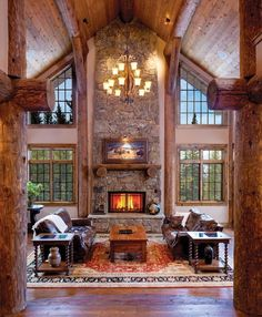Symmetrical log beams and floor-to-ceiling windows frame a two-story stone fireplace in one of Log Cabin Homes Magazine's favorite great rooms