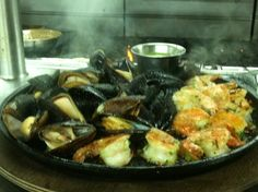 Sizzling Iron Skillet Roasted Mussels and Shrimp at The Franciscan Crab Restaurant - place mussels on a cast-iron skillet and sprinkle with sea salt, cook over high heat until mussels open, discard any that remain closed, place shrimp on an oiled cast-iron skillet and cook for 2 minutes on each side. serve with hot garlic butter sauce for dipping, make the sauce by sauteing butter, roasted garlic, sea salt, white wine and lemon juice 415.362.7733
