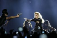 US singer Madonna (R) performs on stage at the Stade de France in Saint-Denis, a Paris suburb, on July 14, 2012, during her MDNA world tour. AFP PHOTO / KENZO TRIBOUILLARD
