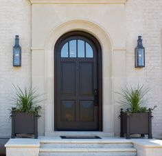 The exterior lighting is by Bevolo. TS Adams Studio Architects. Arched Front Door, Modern Front Door, Exterior Front Doors, Entry Doors, Front Porch, Front Door Lighting, Exterior Lighting, Entry Lighting, Lighting Ideas