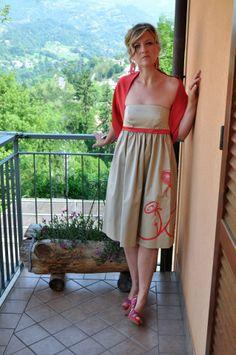 GESSICA  Abito stile impero in cotone lucido dipinto a mano da Moki (collezione FashionArt), motivi floreali sul bordo dell'abito.  Stola ad anello in cadì di seta color corallo. Sul polso indossa un bracciale fiore realizzato con petali in tessuto.