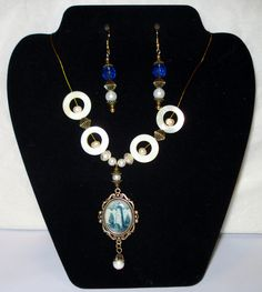 Blue Willow Style Lighthouse Necklace  Earrings Set - Antiqued Bronze  Freshwater Pearls, MOP - FR: Blue Willow Style Lighthouse Necklace  Earrings Set - Antiqued Bronze  Freshwater Pearls, MOP - FREE Shipping! Beautiful necklace features a lighthouse done in Blue Willow style print, and is accented with fire-polished Czech glass rondelles, and mother-of-pearl shells that have freshwater pearl details in the center. Antiqued bronze finish, lobster clasp. Pendant measures 3...