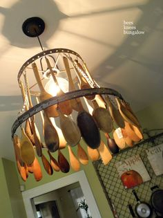 A kitchen objects hanging light. Love those wooden spoons