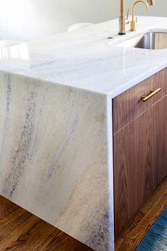 Waterfall island Quartzite countertop, walnut cabinets