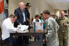 """FORT HOOD — Emeril Lagasse visited the Clear Creek Exchange on Tuesday to sign copies of his book """"Essential Emeril: Favorite Recipes and Hard-Won Wisdom from My Life in the Kitchen."""" More than 100 guests were lined up when Lagasse sat down to sign their books."""