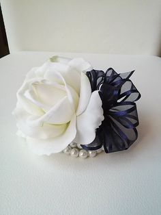Ready to ship beautiful white real touch rose with navy blue ribbon attached to a pearl or rhinestone wristband. Rose is 4x4  Complete
