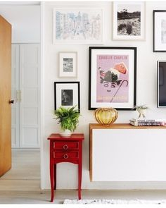 Staging inspiration - plant stand next to modern storage cabinet. Art wall above.